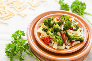 Nutritious pasta with pepper and broccoli on a plate closeup