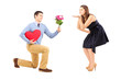 Male on knee giving a heart and flowers to a woman blowing him a