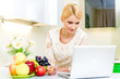 Attractive young woman with computer in the kitchen