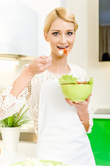 Portrait of a beautiful young woman eating vegetable salad.