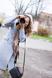 Beautiful girl press photographer or tourist shooting looking at