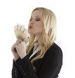 Successful young businesswoman blowing a kiss to euro notes