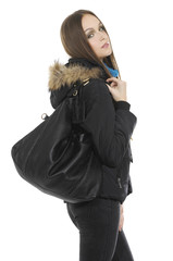 Fashion girl with big bag in coat  posing on gray background