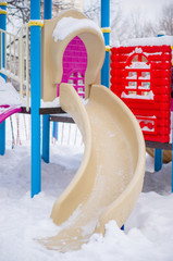 Kids radial slide on winter playground covered with snow