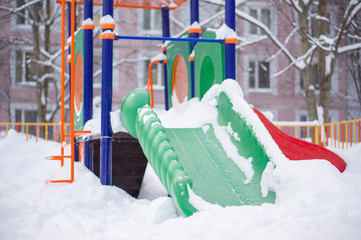 Kids low slide on winter playground covered with snow