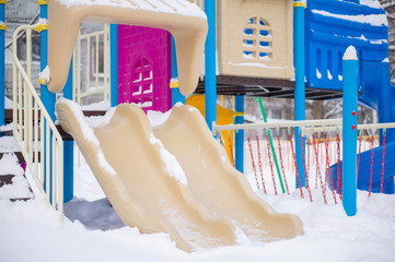 Kids double slides on winter playground covered with snow