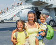 Mother with two kids in front of airplane