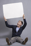 Happy man holding white blank signboard.