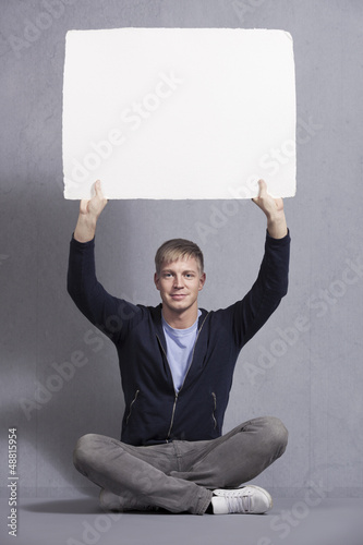 Joyous man holding up white blank panel.