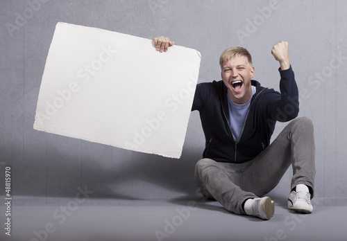 Happy man holding white empty panel.