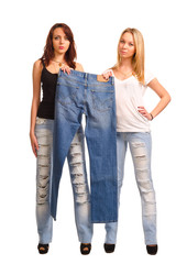 Two young women holding up a pair of jeans