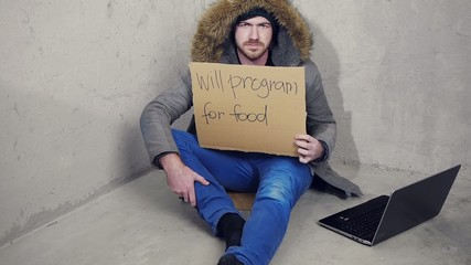 homeless man sitting on the floor with a sign