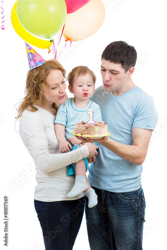 kid with parents celebrating birthday  and blowing candles on ca