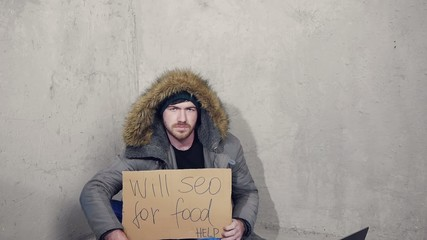 homeless man sitting on the floor with a cardboard asking for a