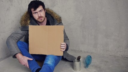 homeless man sitting on the floor with a cardboard