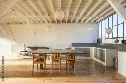 wide room of loft, beams and wooden floor