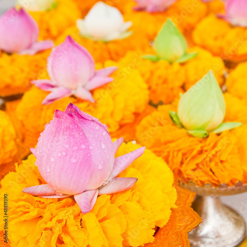 Row of lotus and yellow flower garlands on tray with pedestal in - 48819390