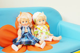 Two dolls sit on a children sofa