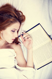 Pretty red-haired woman sleeping in the bed near book. Studio sh