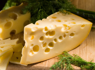 piece of cheese with dill on wooden table