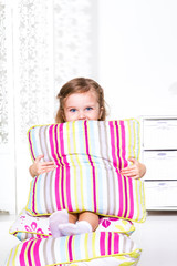 Preschool girl sitting on the pillows