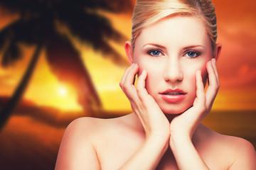junge blonde Frau vor Sonnenuntergang am Strand