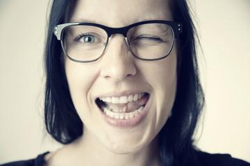 Zwinkernde Frau mit Brille