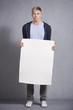 Worried man holding white empty panel.