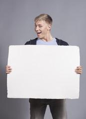 Joyful man presenting white blank signboard.