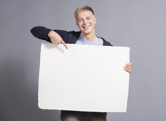 Joyful man pointing finger at white blank panel.