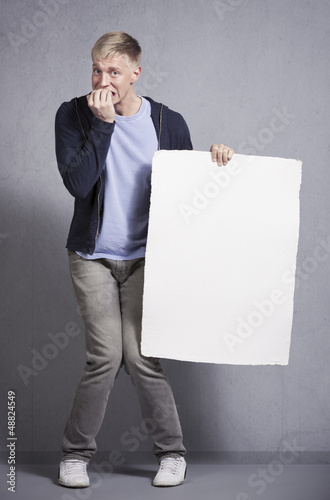 Miserable man holding white empty signboard.