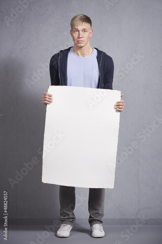 Worried man holding white empty panel.