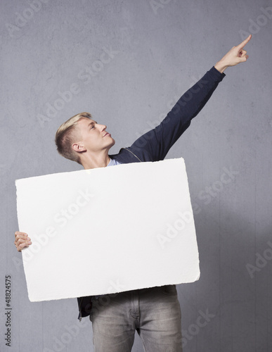 Cheerful man holding white blank signboard.