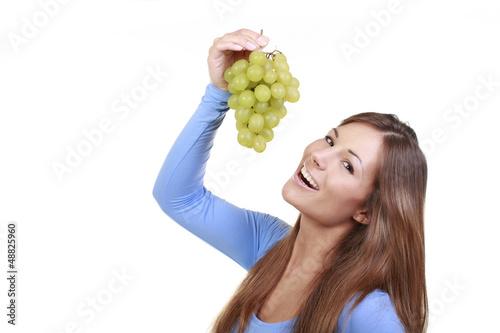 Junge Frau hält grüne Trauben hoch