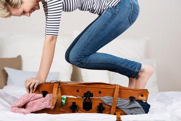 lachende frau steht auf ihrem koffer