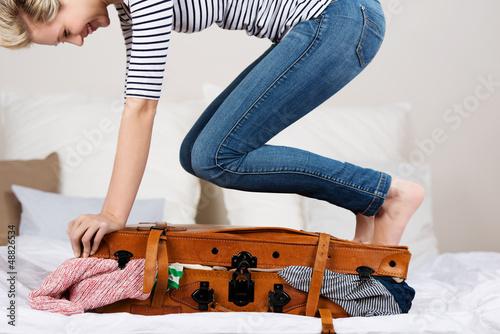 canvas print picture lachende frau steht auf ihrem koffer