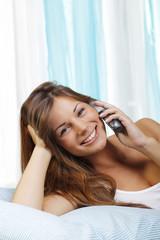 Glückliche Frau telefoniert entspannt im Bett