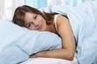 Glückliche Frau liegt im Bett