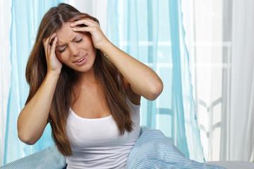 Junge Frau mit Händen am Kopf bei Migräne - Kopfschmerzen