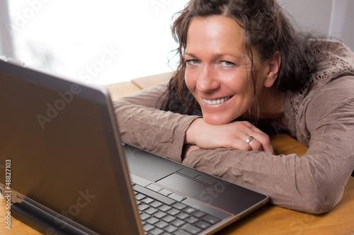 Entspannt lächelnde Frau vor LapTop