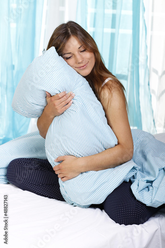 Müde Frau hält ihr Kopfkissen fest