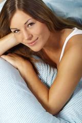 Glückliche Frau im Bett mit freundlichem Blick