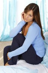 Hübsche Frau sitzt traurig auf dem Bett