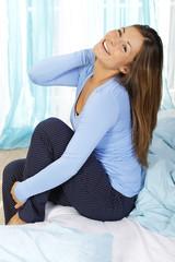 Glückliche Frau sitzt auf dem Bett