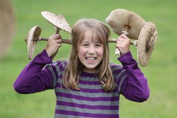 Mädchen mit Riesenschirmpilzen lacht auf der Wiese