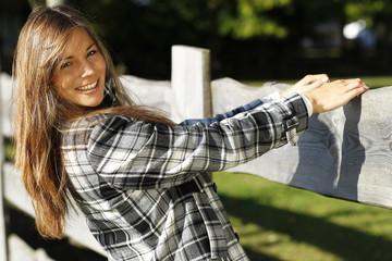 Glückliche Frau hält sich an einem Holzzaun im Grünen