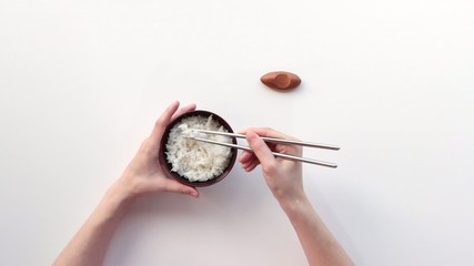 Woman eating rice with chopsticks.