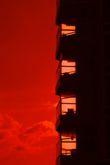 Building silhouette against a burning red sunset