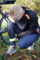Radfahrerin legt Reflektorband an
