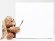 Stuffed bunny peeking behind blank board